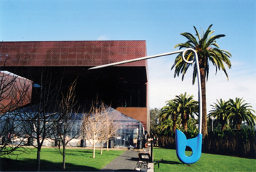 "Claes Oldenburg's giant ""Safety Pin"" and original-site palm trees create a merging of the past and present at the new de Young.`"