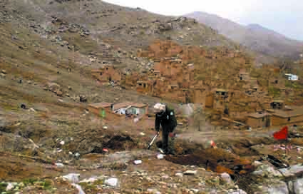 At left, a HALO Afghanistan deminer clears his way up a slope in Guldara district (west of Kabul) in 2006. Now that the slope has been cleared of landmines, residents of the village in the background are using it to graze livestock.