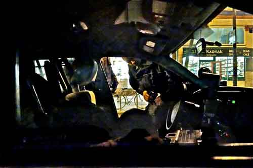 "Officer peers into ""almost stolen"" cop car outside Cafe Med last week. The interior showed signs of a struggle."