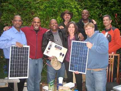 "Assembling ""solar suitcases"" in Stachel's and Aronson's back yard, from left to right: Vander Covington, Matthew Marks Evans, Jabali Nash, Hal Aronson, Laura Stachel, Mark Davis, Mike Strykowski, and neighbor Glen Leggoe who donated materials to the cause."