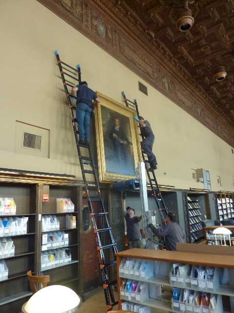 After fasteners were installed, the painting was cranked up the wall, guided by two installers on ladders.