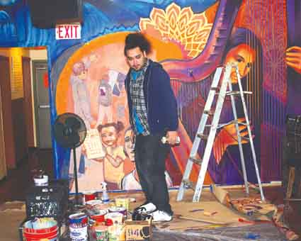 Miguel Perez Bounce, an artist with Trust Your Struggle Collective, works on the group's mural at La Peña Cultural Center on Wednesday. La Peña will hold a dedication for the yet-to-be-named mural as part of its 35th anniversary celebration at noon Sunday at the center at 3105 Shattuck Ave. Admission is free.