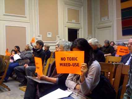 Southside Lofts Neighbor Joslyn Rose holds up a  sign at the Zoning Adjustments Board meeting last Thursday.