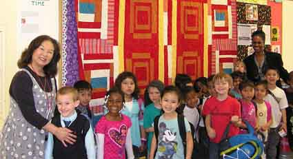 "From left to right, LeConte School kindergarten teacher Ms. Gee, students in her class, Principal Cheryl Wilson, all standing in front of ""We Have a Dream Quilt"" woven in traditional African American style. The quilt will be raffled off on Feb. 26."