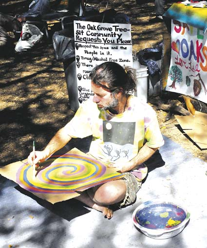 Ayr, one of the ground crewmembers supporting the tree-in protest at the California Memorial Stadium grove, took a painting break Monday afternoon. An archaeological record has raised the possibility of a Native American burial ground at the site. Photo by Richard Brenneman.