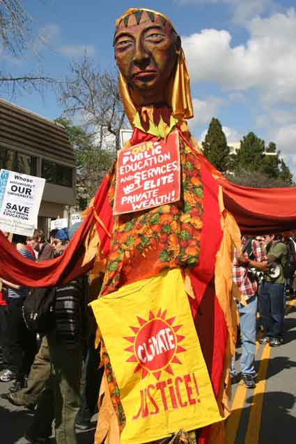 Paper mache dolls, like this one above, dotted the march, making bold statements about the cuts.