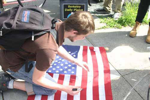 "UC Berkeley student Corey Scher writes the word ""greed"" on an American flag at the corner of Ashby and Telegraph avenues."
