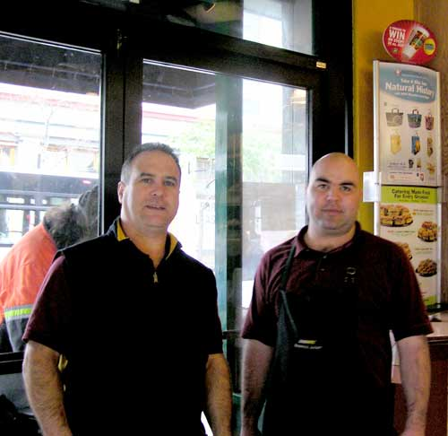 Subway sandwich shop manager Rigo Alonso, left, and worker Servando Gomez, right, stand in front of one of the store's broken windows Wednesday. Alonso said damages arising from the vandalism had cost the store $2,000 so far.
