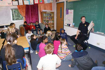 Berkeley Police Department Chief Michael Meehan reads to fifth graders at Washinton Elementary School Friday morning