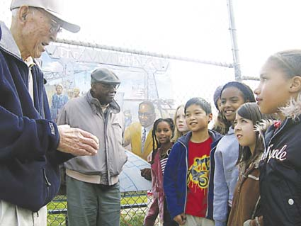 Students from Malcolm X Elementary School listen to Minoru Sano, at left, and Gerald Carter, center, talk about their lives represented in new murals at the school. The mural depicting Carter in behind him. Photograph by Riya Bhattacharjee.