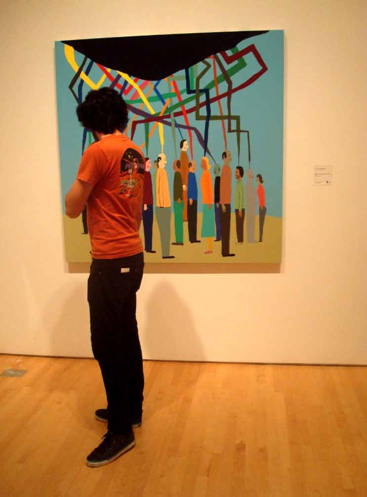 An orange-shirted SF MOMA visitor inadvertently complements the picture he's perusing.