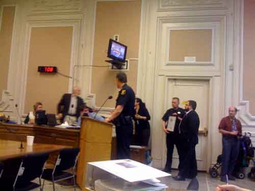 Berkeley Police Chief Mike Meehan looks on as Councilmember Gordon Wozniak gets up to shake hands with Frank Cruz.