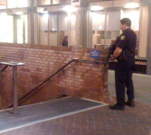 A Berkeley police officer stands with weapon drawn at the Downtown Berkeley BART station entrance on the west side of Shattuck Avenue.