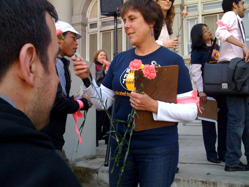 "Berkeley Federation of Teachers Vice President Cynthia Allman hands out pink roses to laid-off teachers at the ""Pink Friday"" rally."