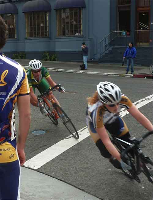Two women racers take the sharp corner onto Bancroft, across from the