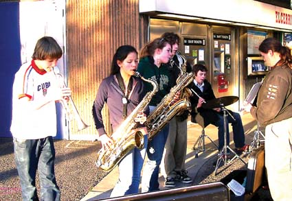 Portola Middle School Music Director Tiffany Carrico (right) leads the school jazz band at the El Cerrito BART Station in preparation for its upcoming concert. Left to right: Aidan Brorsen, trumpet; Caroline Umali, tenor sax; Roschelle Hood, baritone sax; Dan Marsh, tenor sax; Freeman Schlesinger, percussion.
