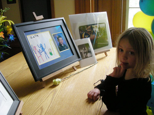 Lily Van-Hout looks at pictures of Zachary Cruz, her fellow student at the Clark Kerr Campus after-school program.