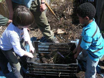Emmett Howard, 7, and Avery Lakes, 6,  learn how to sift compost at the Malcolm X garden.