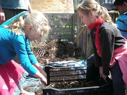 Samantha Myers helps classmate Fay Rauber separate dirt from compost. Malcolm X students grow their own vegetables in the school's garden.