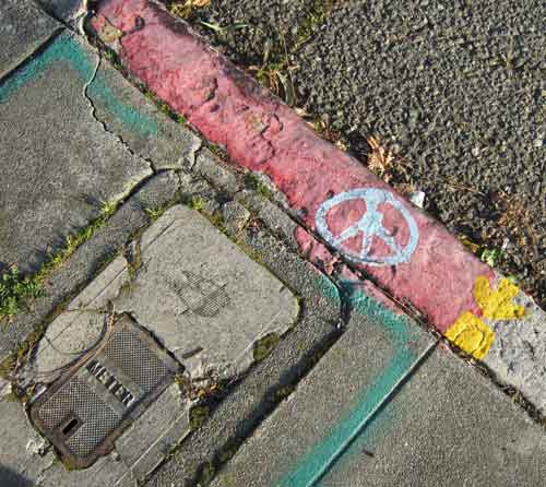 Graffiti most commonly appears on walls, but sometimes a tagger's art-mark can be found directly underfoot -- like this Peace Symbol that adorns a curb near Shattuck and Dwight Way.