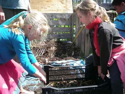 Samantha Myers helps classmate Fae Rauber separate dirt from compost. Malcolm X students grow their own vegetables in the school's garden.