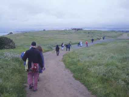 A line of participants winds its way to the hilltop gathering for the Blessing of the Sun in Cesar Chavez Park.