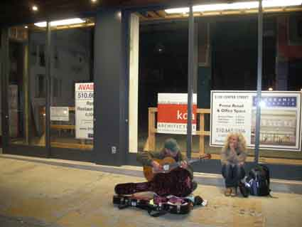 A street musician plays in front of the vacant site of the former Act I & II theater.