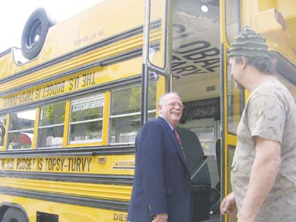 Ben & Jerry's co-founder Ben Cohen boards the Topsy Turvy Bus Wednesday with the vehicle's builder, artist Tom Kennedy, looking on. Photograph by Riya Bhattacharjee.