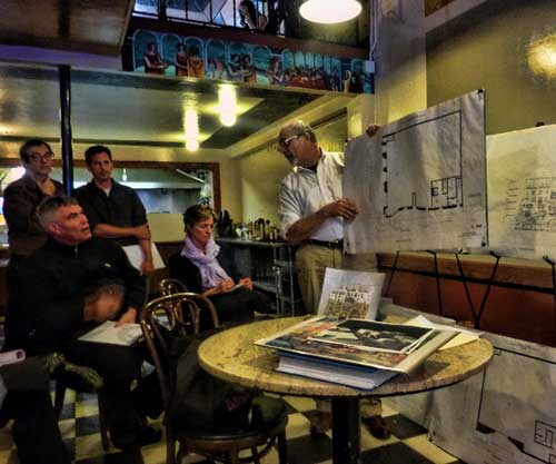 Peterson presents the design concept to a small audience, including site owner and developer Ken Sarachan (far left, standing), in the Cafe Med on Telegraph.