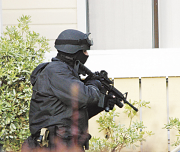 Richard Brenneman: Wearing body armor and carrying a military assault rifle, a Berkeley police officer stands guard outside the Ocean Gardens apartments where a man armed with kitchen knives held off police for 30 hours before surrendering early Thursday..