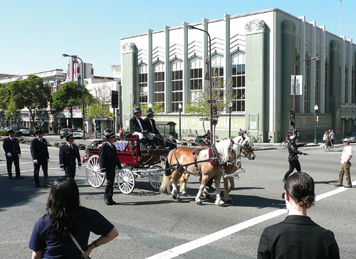 The horse-drawn wagon bearing the body of firefighter Jay Randall Walter rolls past the Berkeley Public Library during the procession that began at Station 5 and ended at St. Joseph the Worker Catholic Church.