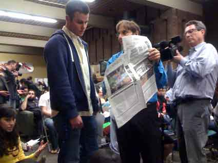 Jews for Justice member Matthew Taylor shows ASUC President Will Smelko the two-page ad his group took out in the Daily Californian Tuesday in support of the divestment bill.