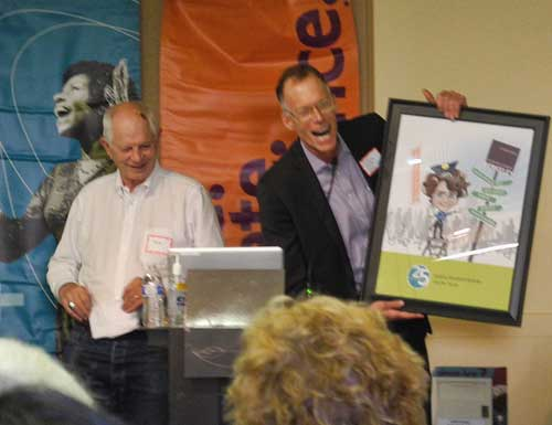 Berkeley Mayor Tom Bates and Downtown Berkeley Association Chief Executive Officer John Caner chortle as they present a commemorative caricature to departing DBA President Susan Medak of the Berkeley Repertory Theater at the DBA's annual meeting.