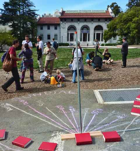 Astronomy students set up a sundial with chalk and book markers next to Mining Circle and solar telescope displays.