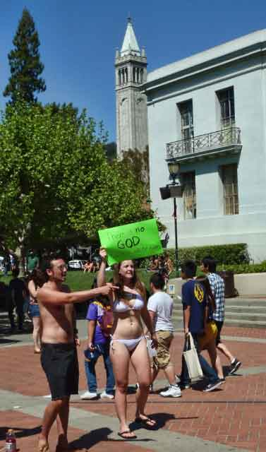 "Bikini clad Cal atheists (""There is no God.  So relax and be happy"") attracted attention in Sproul Plaza."