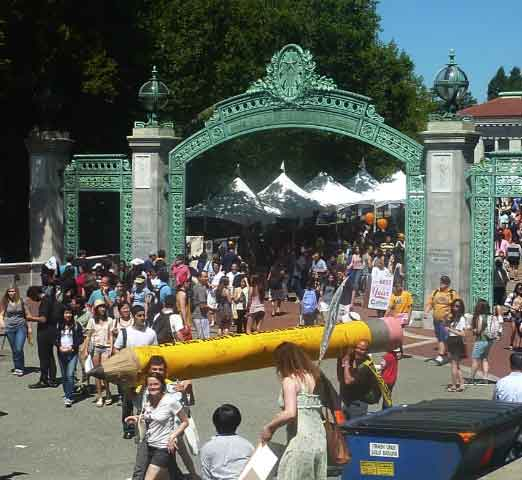 "A giant pencil reading ""Tax The Rich To Teach The Children"" passed in front of a crowded Sather Gate."
