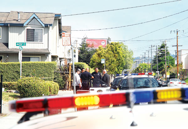 Oakland Police officers confer on the Shattuck Avenue sidewalk in the aftermath of a shooting at a 59th Street home when a resident reportedly shot and seriously wounded an intruder Tuesday morning.