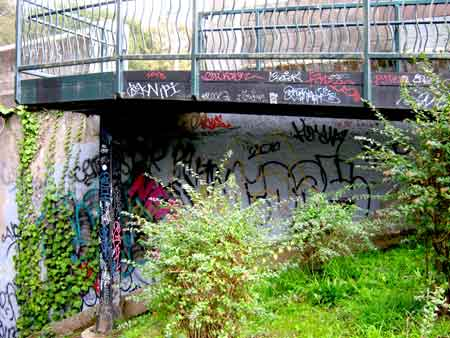 "Colorful swirls of graffiti complement the ivy and flowers covering the concrete walls and metal stairs. (Hard to believe there's a tagger – or band of taggers – that goes by the name ""Nerds."") But look closely at the section of wall on the far right, which features the outline of an unfinished tag."