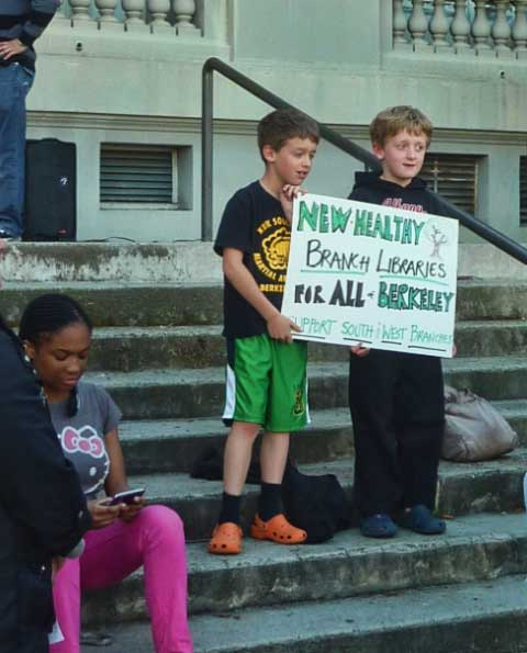 Two boys posed with a sign on the steps of City Hall before the rally.