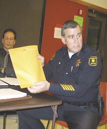 Photograph by Judith Scherr: Berkeley Police Chief Douglas Hambleton shows the Police Review Commission how Sgt. Cary Kent tampered with drug evidence envelopes, through the bottom.
