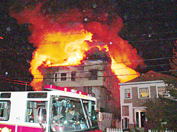 An arson fire engulfed the house on the corner of Shattuck Avenue and Essex Street late Monday night. The property, known as the Flying Cottage had been the center of controversy over a proposed remodeling which raised the building to three stories.