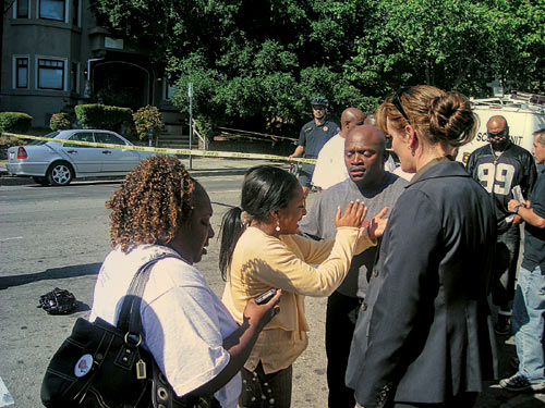 Rita McIntyre (left), mother of Maceo Smith, talks to a police detective right after her son was shot to death near the Douglas Parking Lot in broad daylight Tuesday.