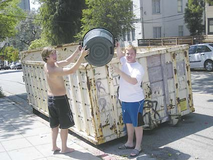 Beta Theta Pi fraternity brothers Chris Wenner, left, and Neill Barrett took advantage of the UC dumpsters in front of their frathouse Thursday to discard their trash. Photograph by Riya Bhattacharjee.