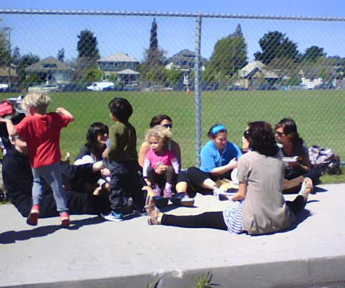 Moms and kids sitting on the Derby sidewalk enjoy the sunshine  at the Farmers' Market.