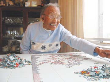 Photograph by Riya Bhattacharjee. Ruby Harmon, in her Berkeley home, said working on her jigsaw puzzle is her favorite activity.