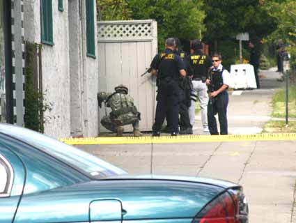 The Berkeley Police Department SWAT team searches for an armed suspect near the corner of Shattuck and Ashby avenues.