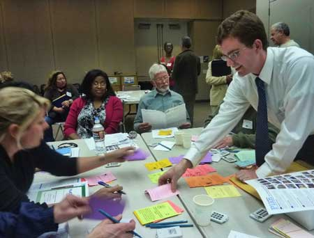 A MTC planner, right, tries to get skeptical participants to rank choices on