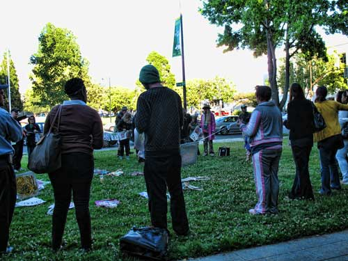 About 100 people gathered in a prayer circle before the Tuesday Berkeley City Council meeting to protest the proposed anti-sitting law, using prayer flags made by Youth Spirit Artworks.