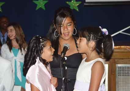"LeConte Elementary School fifth-graders Vanessa Echeveste, Yesenia Bermudez and Zaira Romero lead their classmates and the audience in a rendition of ""What Can One Little Person Do?"" during the school's June 9 promotion ceremony."