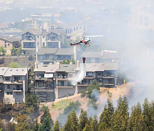 A helicopter drops water scooped from Lake Temescal onto the smouldering embers of a fire that consumed two acres of hillside Thursday near the site where the 1991 Oakland Hills Fire ignited.